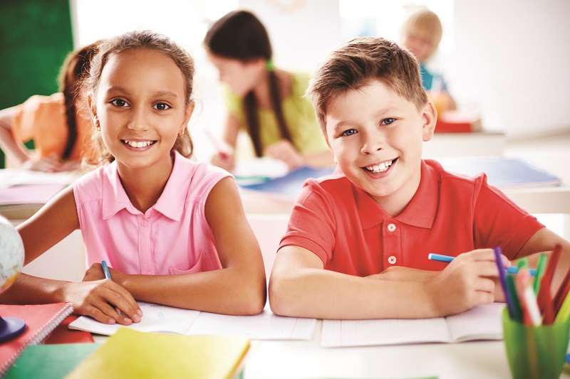 Schoolboy and schoolgirl looking at camera on background of other kids